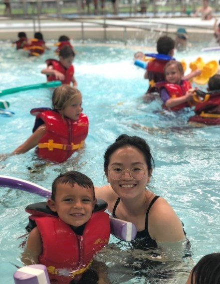 Camp counselor and campers swimming