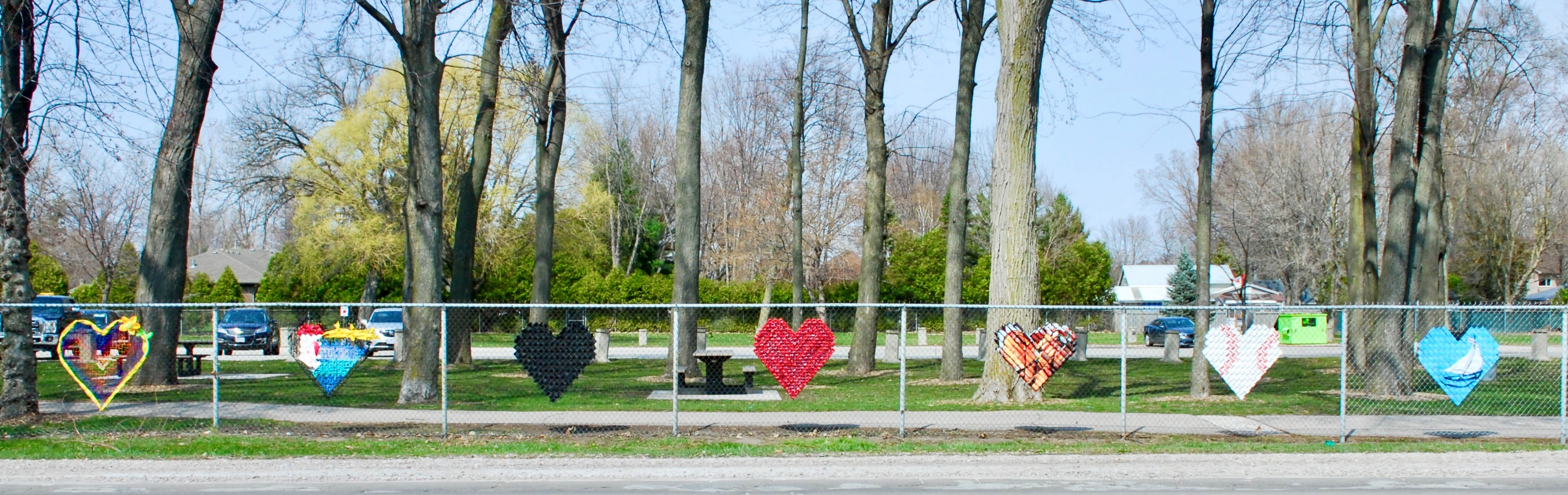 a variety of seven colourful hearts on a fence